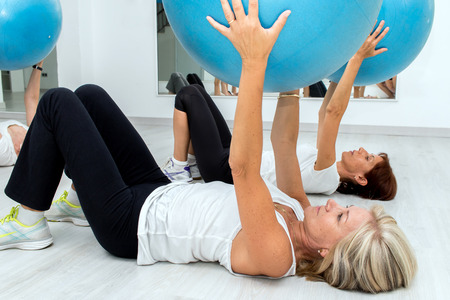 aged: Group of Middle aged women exercising with fitness balls in health center,