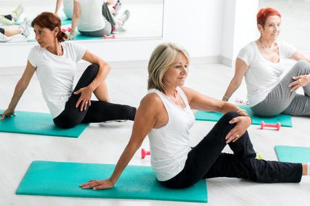 체육관에서 워밍업 중간 나이 든된 여자의 그룹입니다. 고무 매트에 바닥에 앉아하는 잘 생긴입니다.
