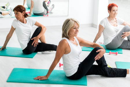 fit: Group of middle aged women warming up in gym.Threesome sitting on floor on rubber mattresses. Stock Photo