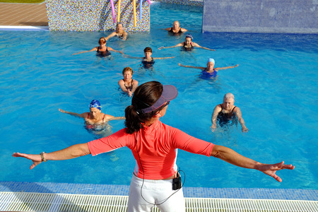 gimnasia aerobica: Cierre de vista trasera del preparador físico en la sesión de la clase mayor de salud en la piscina al aire libre.