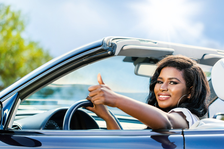 Close up portrait of attractive black female driver doing thumbs up.Young girl sitting in convertible.