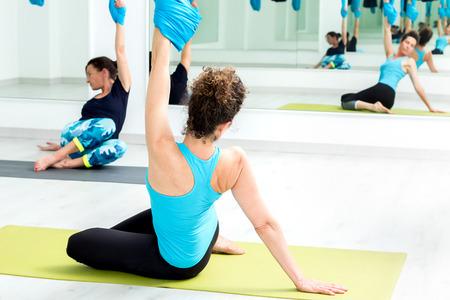gravedad: Cierre de la mujer joven que hace yoga contra la gravedad con telas de algodón en el gimnasio. Foto de archivo