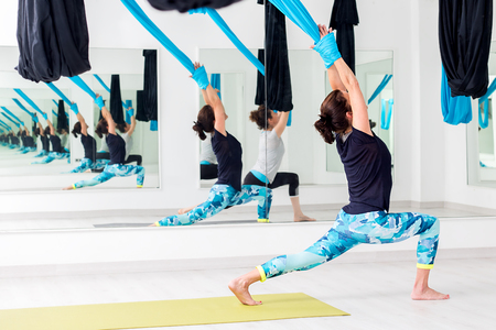 Full length body portrait of young women at aerial yoga session in gym. Stock Photo