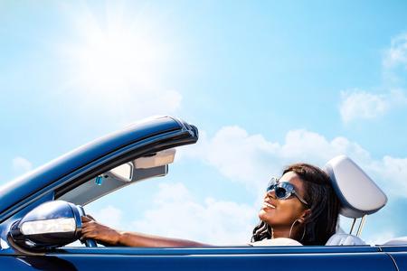 화창한 하늘 아래 컨버터블을 운전하는 매력적인 우아한 아프리카 여자의 초상화를 닫습니다.