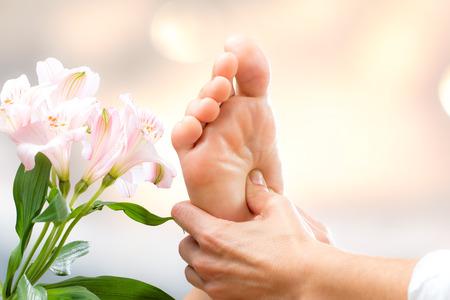Macro vicino di mani che applicano la pressione sul piede femminile.