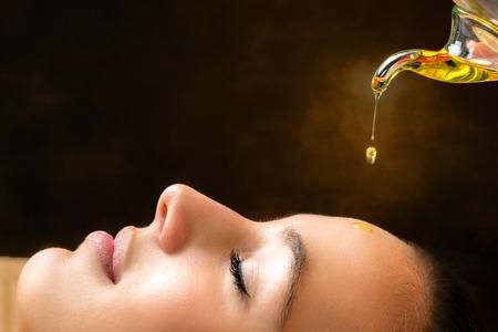 Macro cerca retrato de mujer joven en su sesión de masaje ayurvédico con aceite aromático que gotea en la cara.