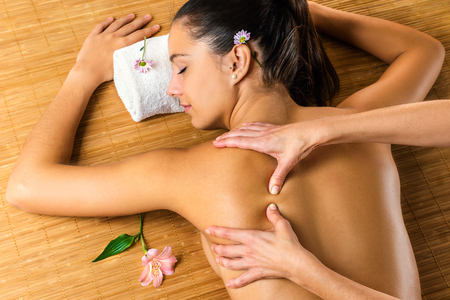healing practitioners: Close up top view of therapist massaging attractive woman.Young girl relaxing in low light spa atmosphere. Stock Photo