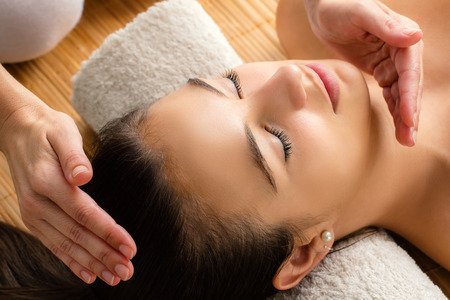 reiki: Close up portrait of attractive woman at reiki session. Therapist healing with hands next to head. Stock Photo
