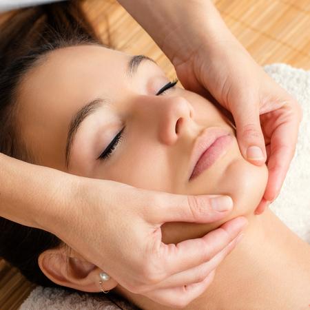 Cerca de retrato de masaje facial relajante en la barbilla femenina. Foto de archivo