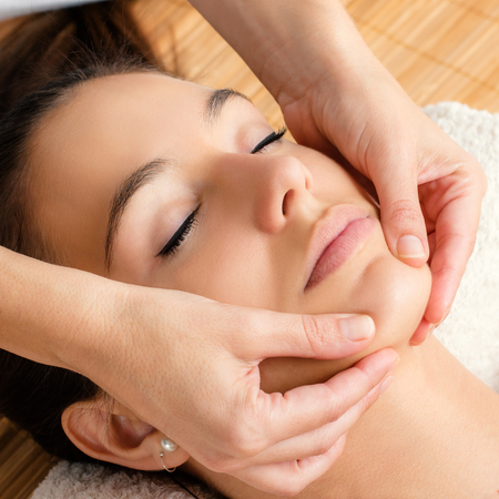 discomfort: Close up portrait of Relaxing facial massage on female chin. Stock Photo