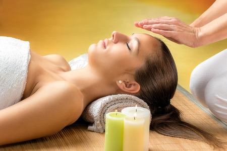 Close-up portret van aantrekkelijke jonge vrouw met een alternatieve behandeling therapie. Therapeut de handen op het voorhoofd van de vrouw.
