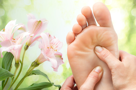 Macro close up of foot massage next to colorful flowers and green background.