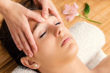 Close up portrait of attractive woman having facial massage.Therapist massaging face with hands. Stock Photo