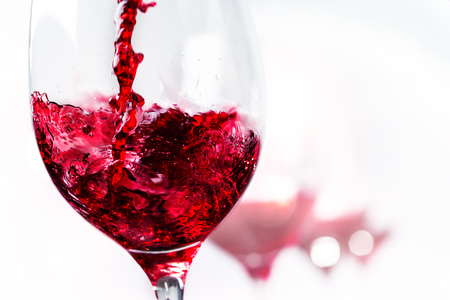 Extreme close up of red wine pouring into glass.Isolated on white background.