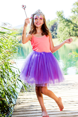 angelical: Close up full length fantasy portrait of little girl holding magic wand next to lake. Stock Photo