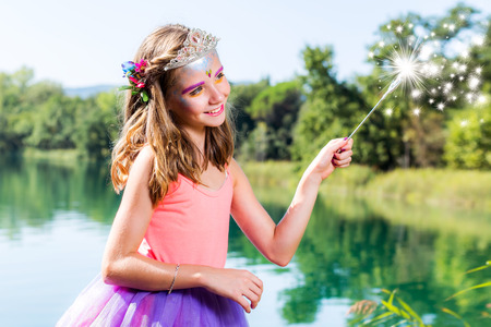 angelical: Conceptual beauty portrait of little girl dressed up as little princess. Girl casting spell with magic wand next to lake.