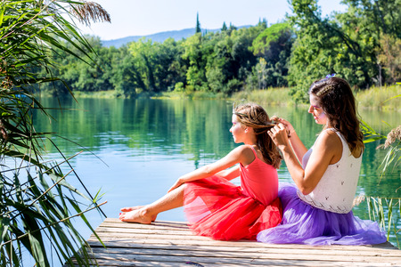 dressed up: Portrait of two girls relaxing on wooden deck next to lake.Girls dressed up in colorful  dresses. Stock Photo