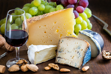 Close up still life cheese variety with red wine, fruits and nuts on wooden table.