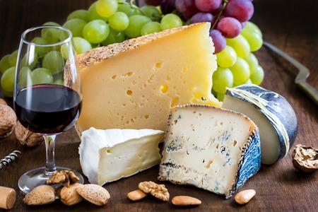 Primo piano ancora varietà vita formaggio con vino rosso, frutta e noci su tavola di legno. Archivio Fotografico