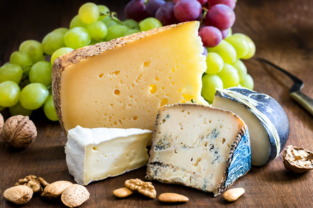 Close up assortment of Appetizing cheeses with nuts and grapes on wooden surface.