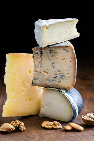 morsel: Close up pile of appetizing cheese variety on wooden surface.Portions of cheese stacked on top of each other.