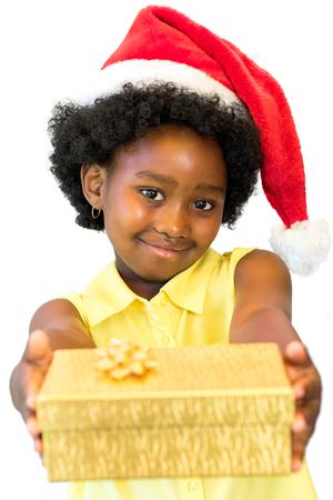 Sluit omhoog portret van weinig Afrikaans meisje die rode Kerstmishoed dragen die gouden doos houden. Geïsoleerd op witte achtergrond.