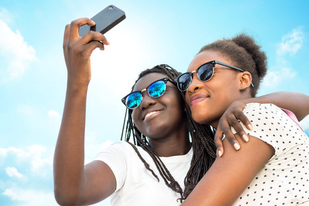 Close up portrait of two diverse african teen girls wearing sun glasses taking self portrait with phone against blue sky. Stock Photo