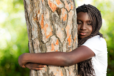 fullness: Close up portrait of african teen girl with braided hairstyle embracing tree in woods. Stock Photo
