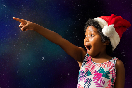 Close up conceptual portrait of cute african girl pointing at stars.Excited child with open mouth wearing christmas hat against dark star background.