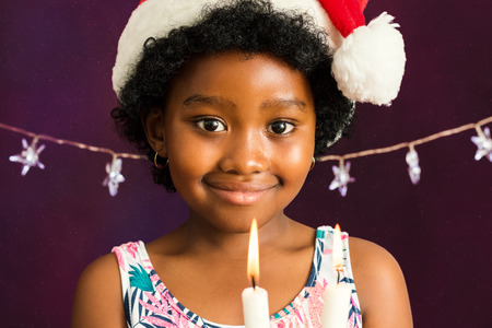 face shot: Close up face shot of little afro american girl with christmas hat holding candles. Stock Photo