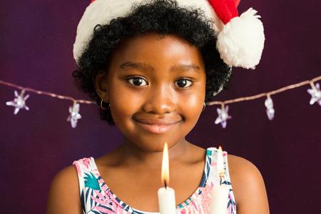 Close up Gesicht Schuss kleines afroamerikanisch Mädchen mit Hut Weihnachten Kerzen halten.