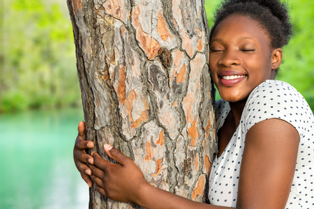 fullness: Close up portrait of african girl embracing tree in woods. Stock Photo