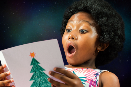 face shot: Close up face shot of little african girl reading a christmas card with surprised face expression.Excited kid with mouth open against galaxy star background.