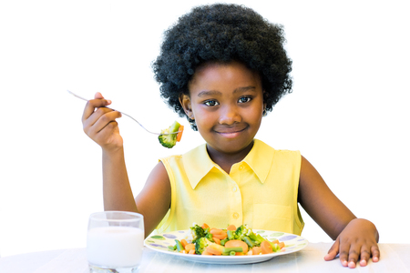 Close up portrait of cute african girl with afro hairstyle eating healthy vegetable dish. Isolated on white.