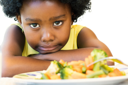 long faced: Close up face shot of little afro american girl with negative moody face expression at dinner table. Kid pulling funny face with vegetable dish in foreground. Isolated on white.