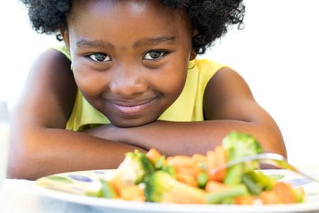 niña comiendo: De cerca la cara de foto de niña africana lindo delante del plato de verduras saludables. Aislado en blanco. Foto de archivo