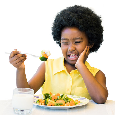 Close up portrait of little black girl refusing vegetable meal at dinner table.Isolated on white background. Stock Photo