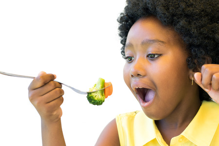 Close up portrait of little african girl taking a bite of broccoli and carrot. Isolated on white.