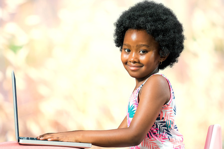 pre schooler: Close up portrait of little african girl with afro hairstyle typing on laptop against colorful background. Stock Photo