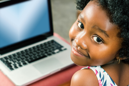 pre schooler: Close up face shot of little african girl with laptop in background. Stock Photo