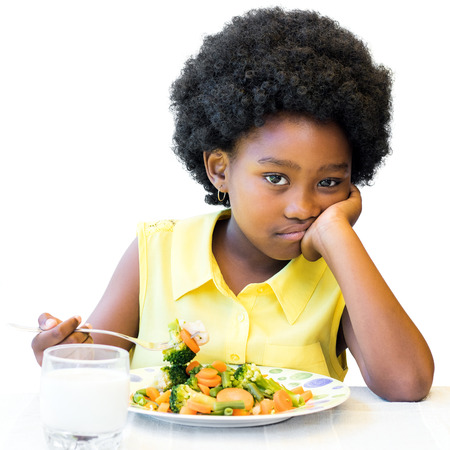 Close up portrait of little african girl sitting in front of healthy vegetable dish.Long faced kid with afro hairstyle Isolated on white background.