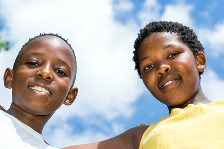 face shot: Close up low angle face shot of two african kids together against blue sky wit clouds.