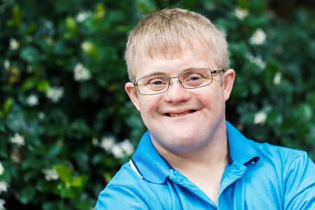 Close up face shot of friendly young man with down syndrome against outdoor green background.