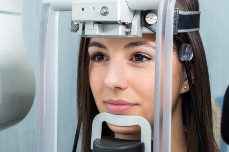 Sluit omhoog gezicht van meisje met hoofd wordt geschoten in cephalometrische panoramische x-ray machine die wordt geplaatst.