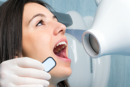 Close up portrait of young woman with open mouth next to x-ray machine in dental clinic.Assistant holding blank x-ray in front of girl.  Stock Photo