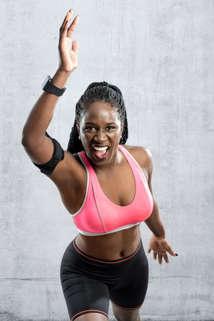 vigorous: Medium shot of black female athlete in take off position. Young woman with vigorous face expression with hands in air against grey concrete background.
