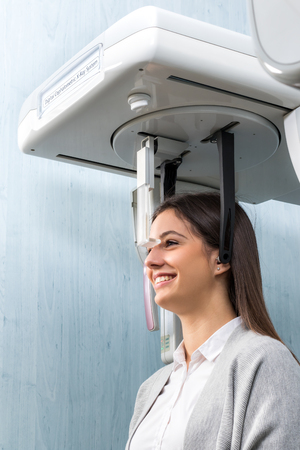 Close up side view portrait of woman taking dental examination with digital cephalometric x-ray machine in clinic. photo