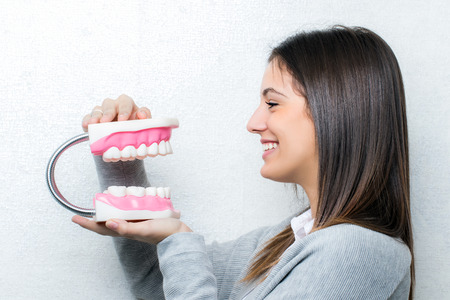 Close up portrait of attractive young girl holding oversize human teeth prosthesis.Side view of woman against light textured background. photo