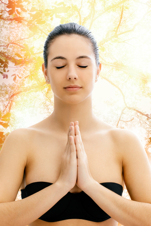 fullness: Close up conceptual portrait of young woman meditating with tree in background.Girl with eyes closed and hands together in front of chest.