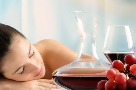 Sluit omhoog portret van rode wijnkaraf en tros van druiven met vrouw op achtergrond Jong meisje die in wine spa leggen.